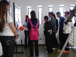 Imagem da Exposição sobre Astronomia com alunos atentos às explicações das alunas responsáveis